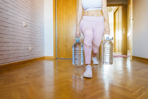 Low section of woman practicing lunges with water bottles during weight training at home - JCMF00651