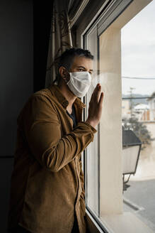 Man wearing protective mask and looking out of the window - RCPF00231