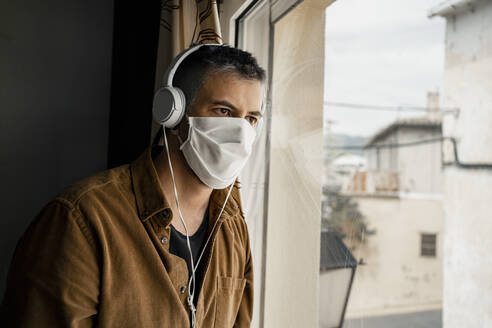 Man wearing protective mask and white headphones looking out of the window - RCPF00234