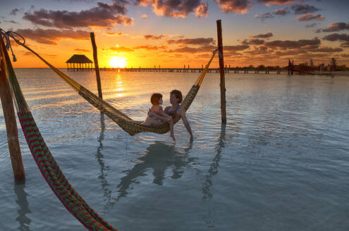 Mother and daughter relaxing on hammock at beach during sunset in Holbox Island, Cancun, Mexico - DSGF02015