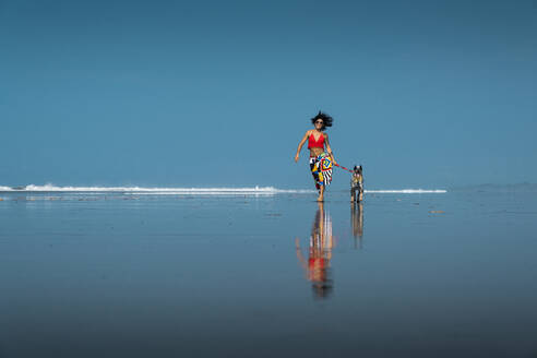 Carefree young woman taking her dog for a walk at the beach, Costa Rica - AMUF00093