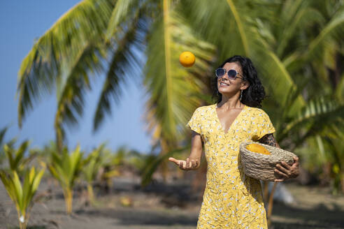 Young woman holding a fruit basket at the beach, Costa Rica - AMUF00099