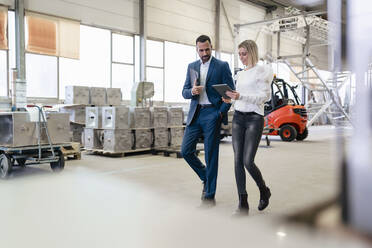 Businessman and young woman with tablet walking and talking in a factory - DIGF09950