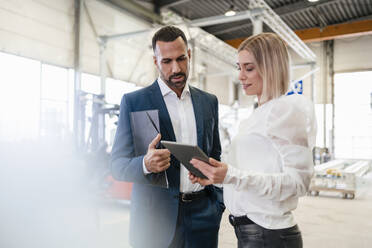 Businessman and young woman with tablet talking in a factory - DIGF09953