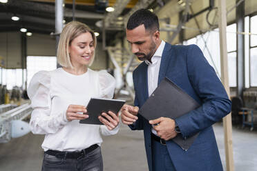 Businessman and young woman with tablet talking in a factory - DIGF09956