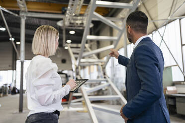 Businessman and young woman with tablet talking in a factory - DIGF09959
