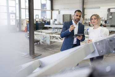 Businessman and young woman talking in a factory - DIGF09965