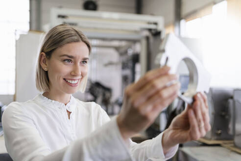 Smiling young woman holding workpiece in a factory - DIGF09986