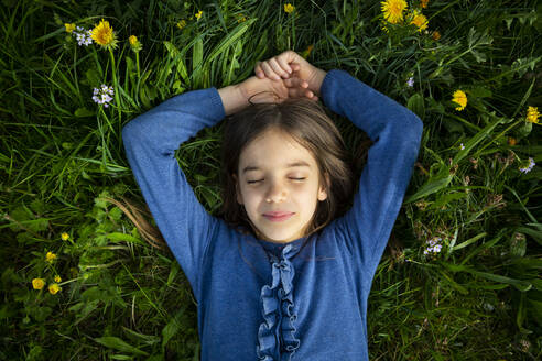 Portrait of girl with eyes closed relaxing on a meadow in spring - LVF08851