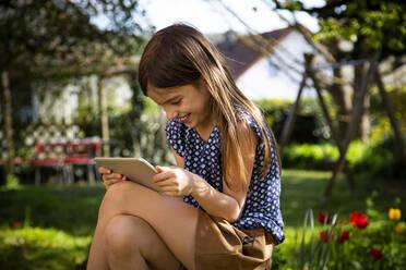 Happy girl sitting in garden using digital tablet - LVF08861