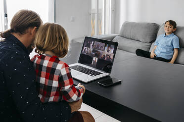 Father with daughter having a video chat at desk with son in background - JRFF04382