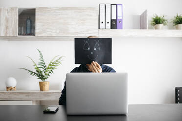 Man working at home with a black cardboard covering his face - JRFF04397
