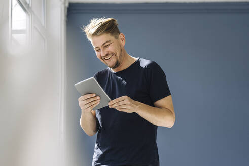 Happy man using a tablet at the window - JOSEF00509