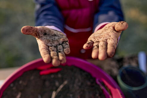 Close-up of girl showing her dirty hands from gardening - ZEDF03333
