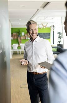 Mature businessman brainstorming at blackboard in office - PESF01945