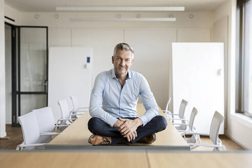 Portrait of confident mature businessman sitting on table in conference room - PESF01993