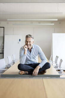 Portrait of smiling mature businessman sitting on table in conference room - PESF01996