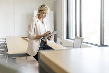 Blond businesswoman using tablet in conference room - PESF01999