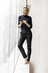 Casual businesswoman holding cell phone at the window - PESF02011