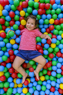 Smiling girl lying in ball pit - MGIF00910