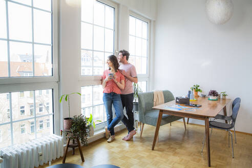 Couple standing at the window at home looking out - FKF03744