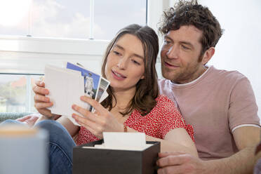 Couple looking at photographs at home - FKF03747