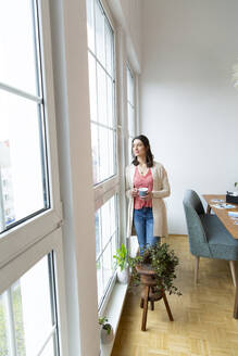 Woman standing at the window at home looking out - FKF03756