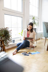 Woman sitting on the floor at home looking at photographs - FKF03759