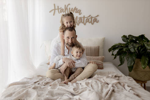 Family portrait of happy father sitting on bed  with his two children - GMLF00119