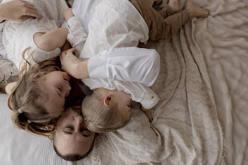 Father lying on bed cuddling with his two children - GMLF00122
