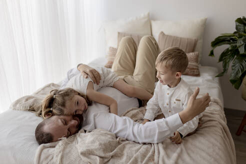 Father lying on bed cuddling with his two children - GMLF00125