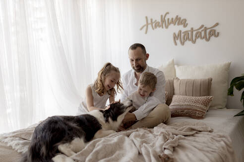 Portrait of happy father sitting on bed with his two children stroking the dog - GMLF00137