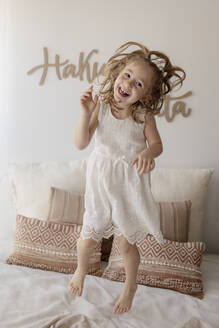 Portrait of happy little girl jumping on bed - GMLF00164