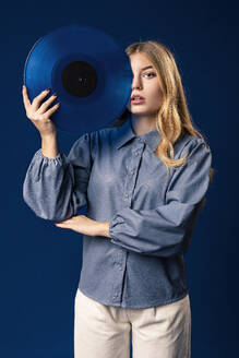 Blond woman with blue record in front of blue background - AGGF00055