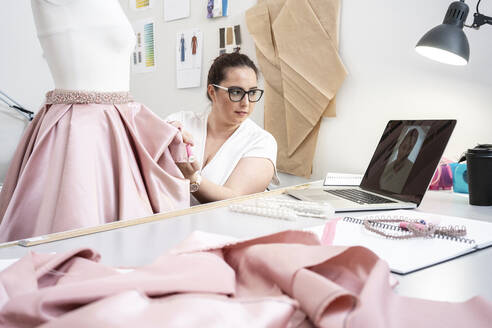 Seamstress working in tailor shop and presenting skirt via video call - VPIF02361