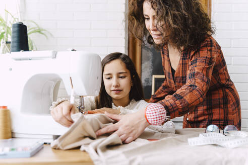 Mother and daughter sewing at home - ERRF03565
