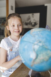 Portrait of smiling girl looking at globe - HMEF00917