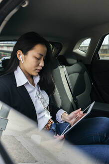 Young businesswoman sitting in car using earpods and digital tablet - XLGF00116