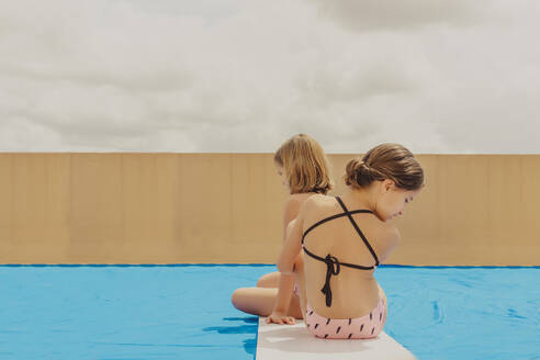 Back view of two girls playing swimmingpool on roof terrace - ERRF03591