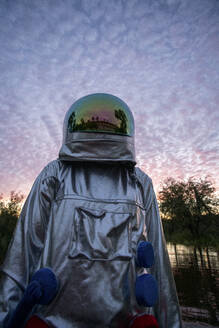 Portrait of spacewoman looking up at sunset - VPIF02402