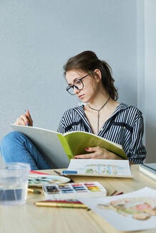 Millennial girl draws fabulous images on paper while sitting at home - CAVF80612