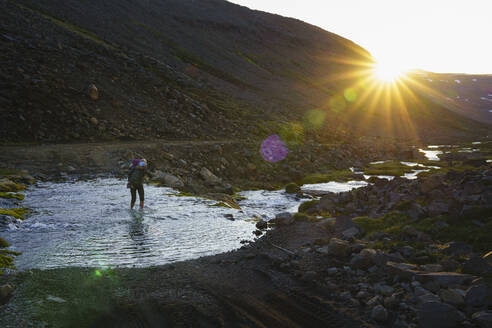 Famale Backpacker Crossing Glacial River In Iceland Highlands - CAVF80639