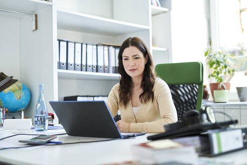 Businesswoman using laptop at desk in office - MMIF00203