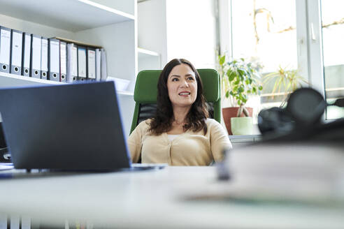 Thoughtful businesswoman with laptop sitting at desk while looking away in office - MMIF00206