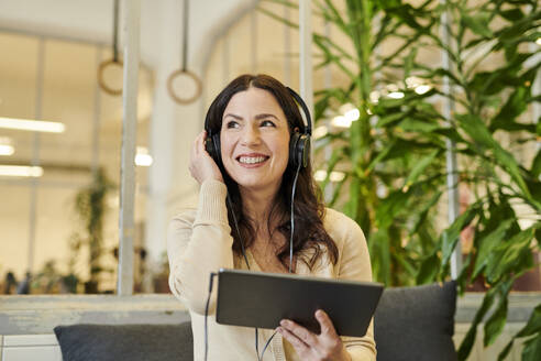 Smiling businesswoman listening music on headphones through digital tablet at office - MMIF00215