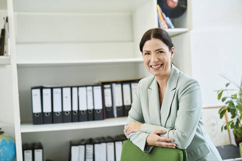 Confident smiling female professional standing on office chair at office - MMIF00233