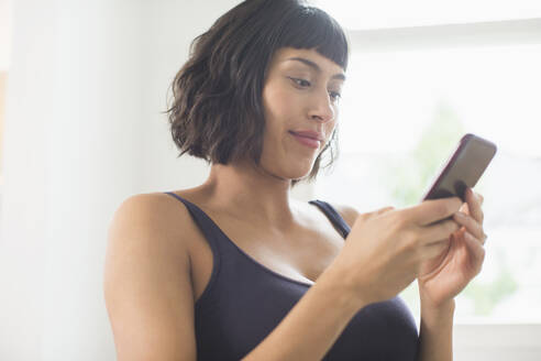 Woman in bra using smart phone - HOXF06241