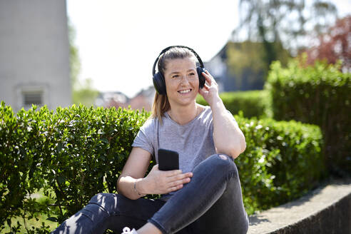 Smiling woman looking away while listening music through headphones on smart phone by plants - MMIF00251