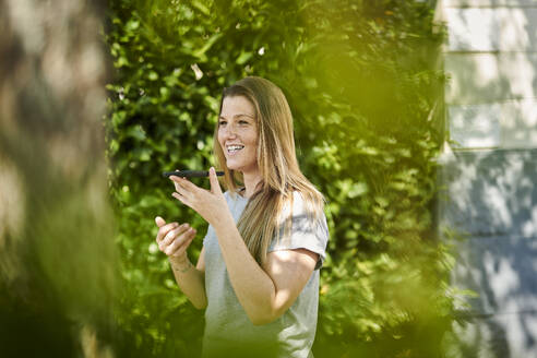Smiling woman talking on speaker over smart phone while standing amidst plants in backyard - MMIF00254