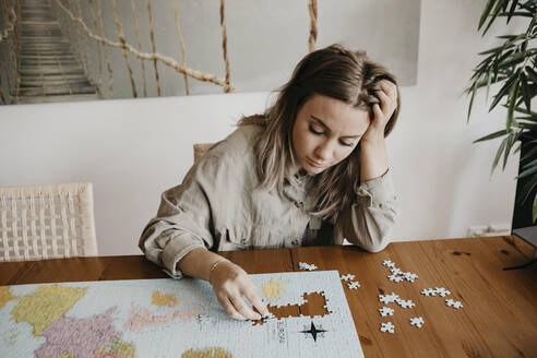 Confused woman playing with jigsaw puzzle at table during home quarantine - LHPF01266